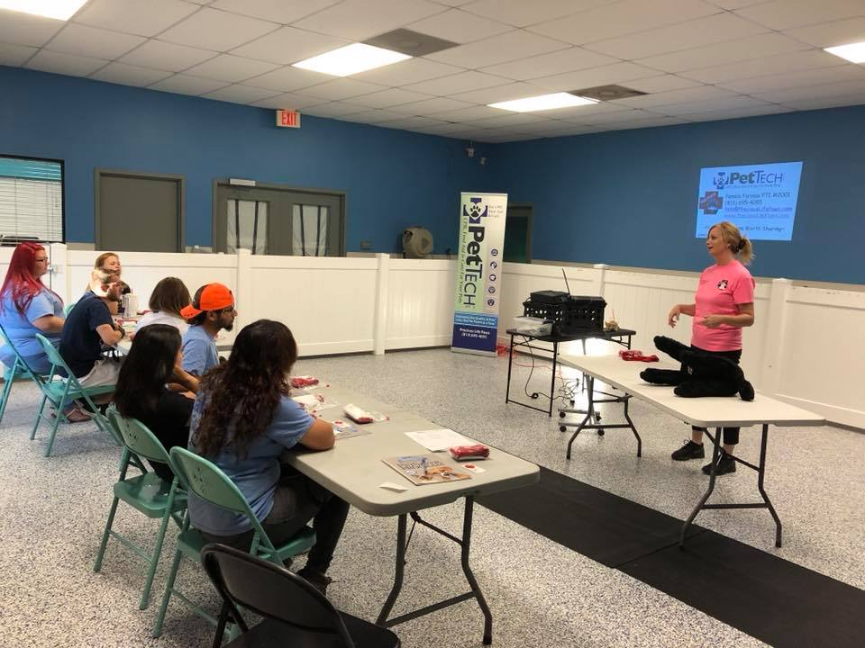 PetTech educator teaching a group of animal care pros at Canine Cabana